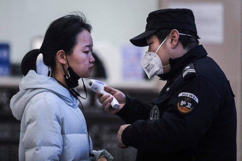 Security personnel check the temperature of passengers at the wharf on the Yangtze River in Wuhan, China, on Jan. 22.