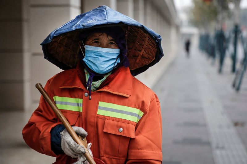 A woman wears a mask while cleaning in the street in Wuhan, China, on Jan. 22.