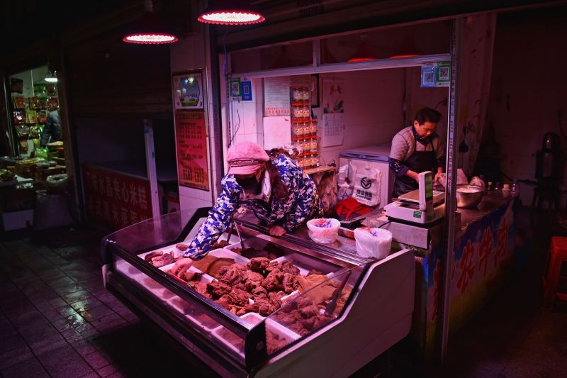 A vendor (C) wearing a facemask offers meat at a near-empty market on the eve of the Lunar New Year in Wuhan on January 24, 2020.