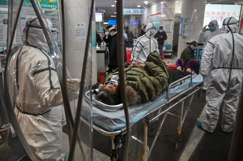 Medical staff members, wearing protective clothing to help stop the spread of a deadly virus that began in the city, arrive with a patient at the Wuhan Red Cross Hospital in Wuhan, China, on Jan. 25.