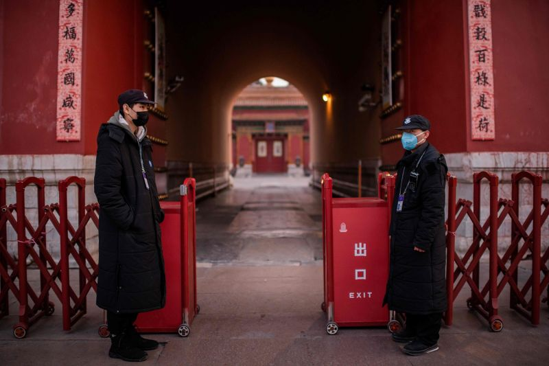 Security guards wearing protective face masks stand at the exit of the Forbidden City in Beijing on Jan. 25.
