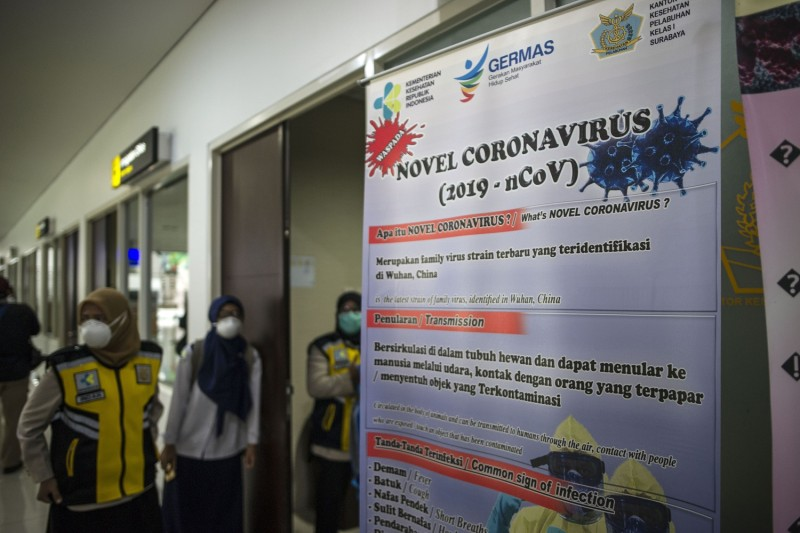 Indonesian health officials stand next to a banner showing information about the Wuhan coronavirus at Juanda International Airport in Sidoarjo, East Java, on Jan. 30.