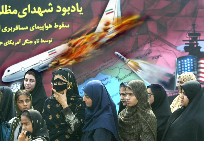 Relatives of victims of the Iranian Airbus shot down by a U.S. Navy cruiser in 1988 over Persian Gulf waters stand under a painting depicting the scene during a ceremony in the Iranian port of Bandar Abbas on July 3, 2003.