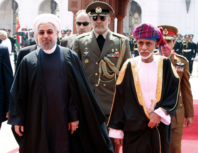 Then-Omani leader Sultan Qaboos and Iranian President Hassan Rouhani review the honor guard during a welcome ceremony in Muscat, Oman, on March 12, 2014.
