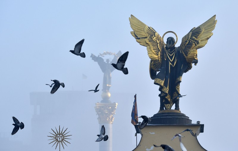 Pigeons fly next to monuments on a foggy day in central Kyiv, Ukraine, on Jan. 17, 2017.