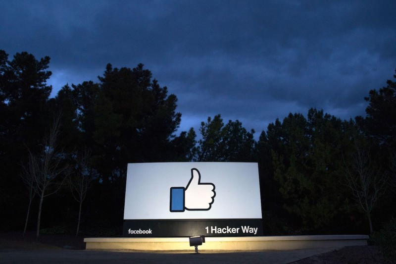 A lit sign is seen at the entrance to Facebook's corporate headquarters in Menlo Park, California, on March 21, 2018.