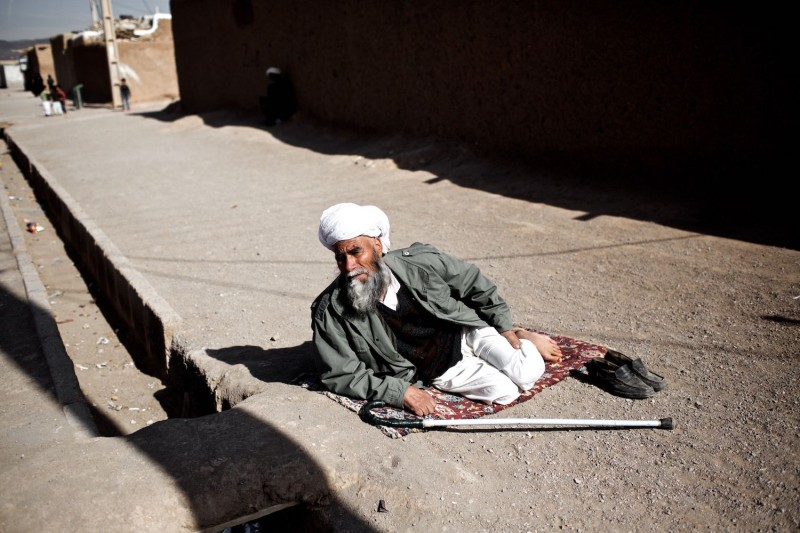 An Afghan man rests in the sun on the road inside the Shahid Nasseri refugee camp near the city of Saveh, Iran, on Feb. 8, 2015.