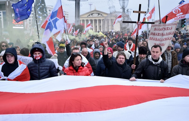 People carry a giant Belarusian historical white-red-white flag during a rally against a Belarusian-Russian integration project in Minsk on Dec. 7, 2019.
