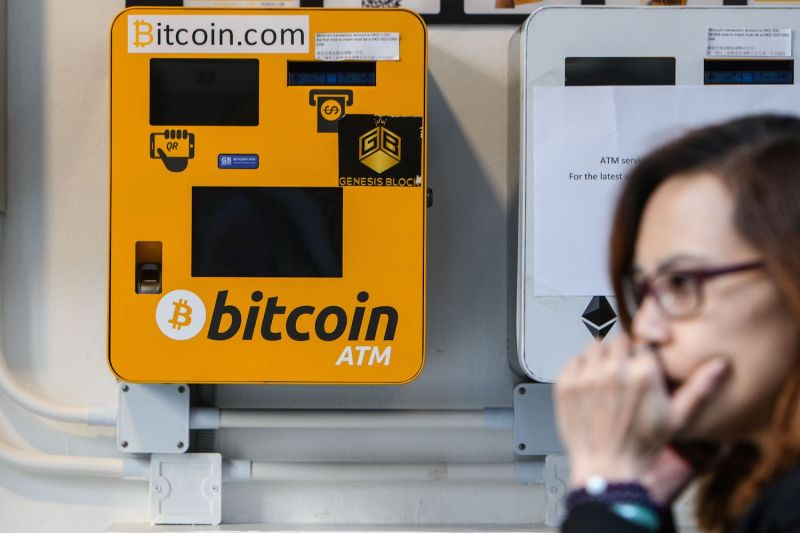 A woman uses her phone as she walks past an ATM for the digital currency bitcoin in Hong Kong on Dec. 18, 2017.