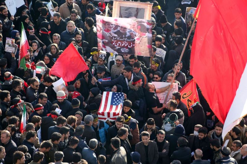 Iranian protestors carry a symbolic coffin wrapped in a U.S. flag during the funeral procession of Gen. Qassem Suleimani in Tehran on Jan. 6.
