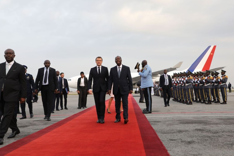 French President Emmanuel Macron is greeted by Ivoirian President Alassane Ouattara at the Félix Houphouët-Boigny International Airport in Abidjan, Ivory Coast, on Dec. 20, 2019.