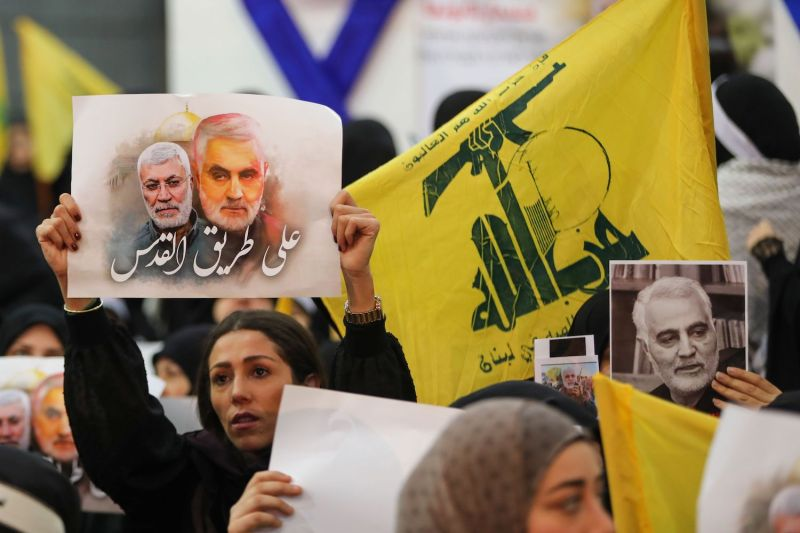 Supporters of the Shiite Hezbollah movement hold a poster of slain Iraqi paramilitary chief Abu Mahdi al-Muhandis and Iranian Major General Qassem Suleimani and Hezbollah flags as the movement's leader delivers a speech in Beirut on Jan. 5.