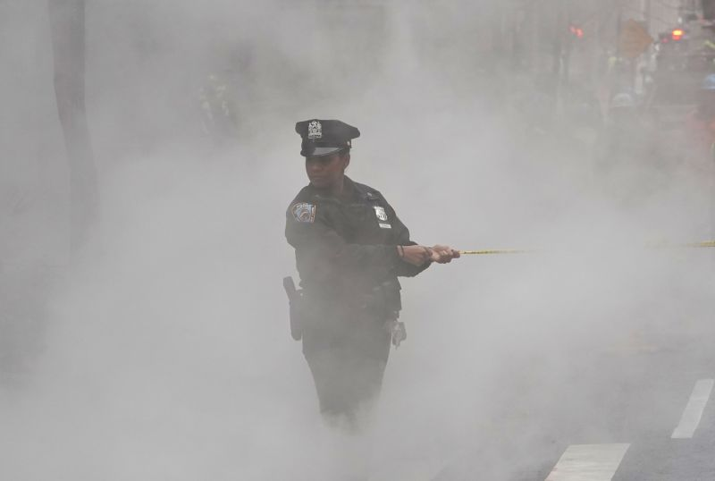 A New York City police officer stands in fog after a water main break on Broadway in New York on Jan. 13.