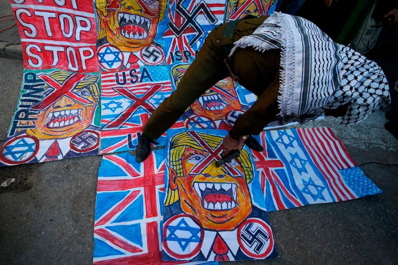 A Palestinian demonstrator points a toy gun at a cartoon drawing depicting U.S. President Donald Trump during a protest against his Middle East peace plan on Jan. 27.