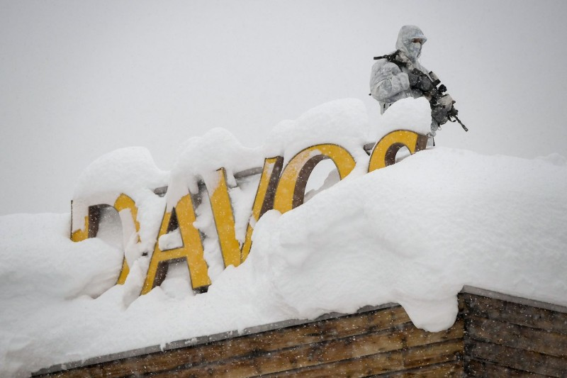 "An armed security guard stands on the rooftop of a hotel, next to letters covered in snow reading ""Davos,"" ahead of the opening of the 2018 World Economic Forum in Davos, Switzerland, on Jan. 22, 2018."