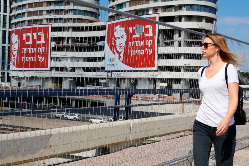 A woman walks past electoral billboards bearing a portrait of Israeli Prime Minister and Likud party chairman Benjamin Netanyahu in Tel Aviv, Israel, on Sept. 4, 2019.