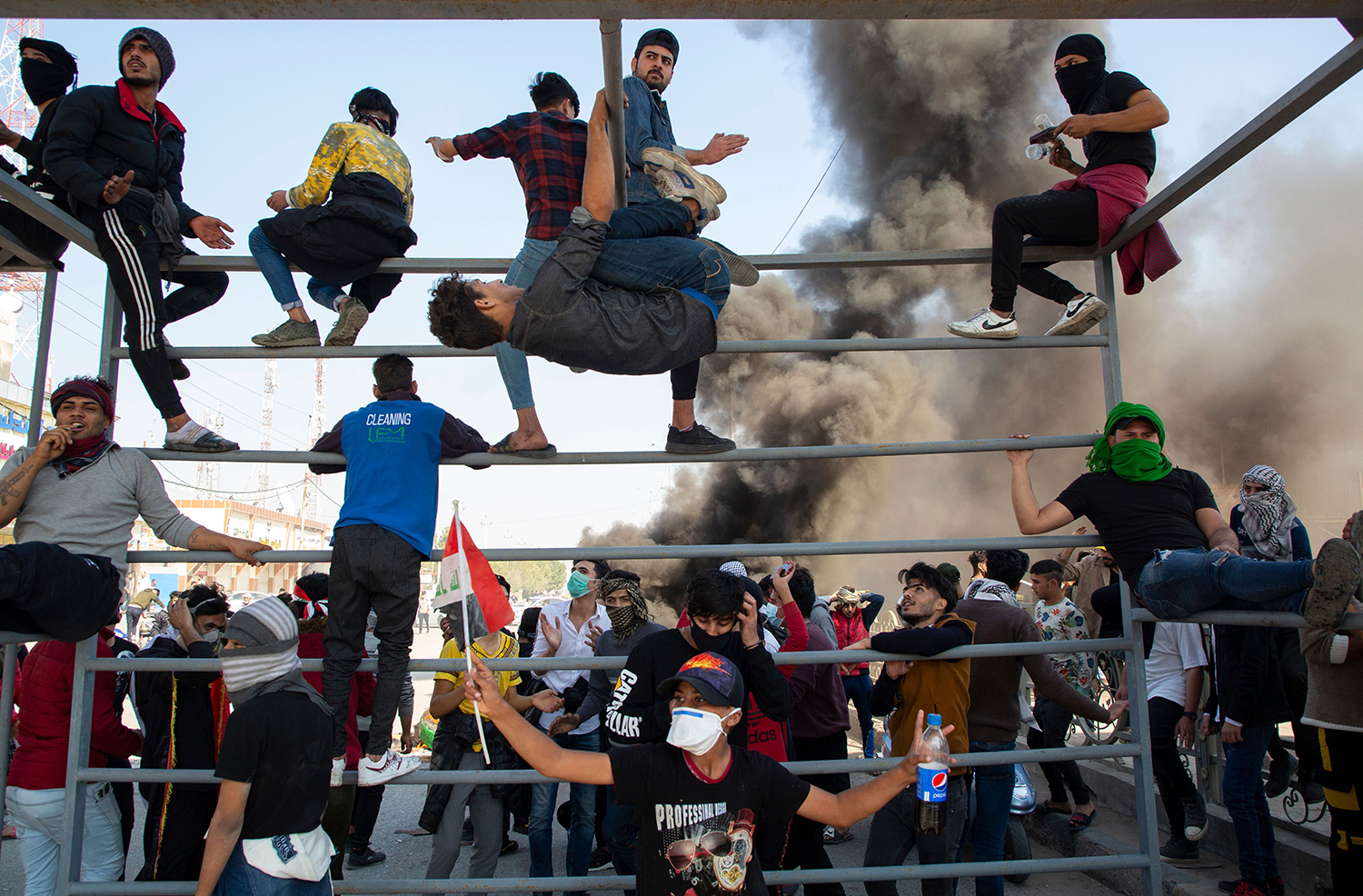 Protesters climb the metal beams of a former advertisement frame  used as a makeshift roadblock during clashes with security forces in Iraq's southern city of Basra on Jan. 20. HUSSEIN FALEH/AFP via Getty Images