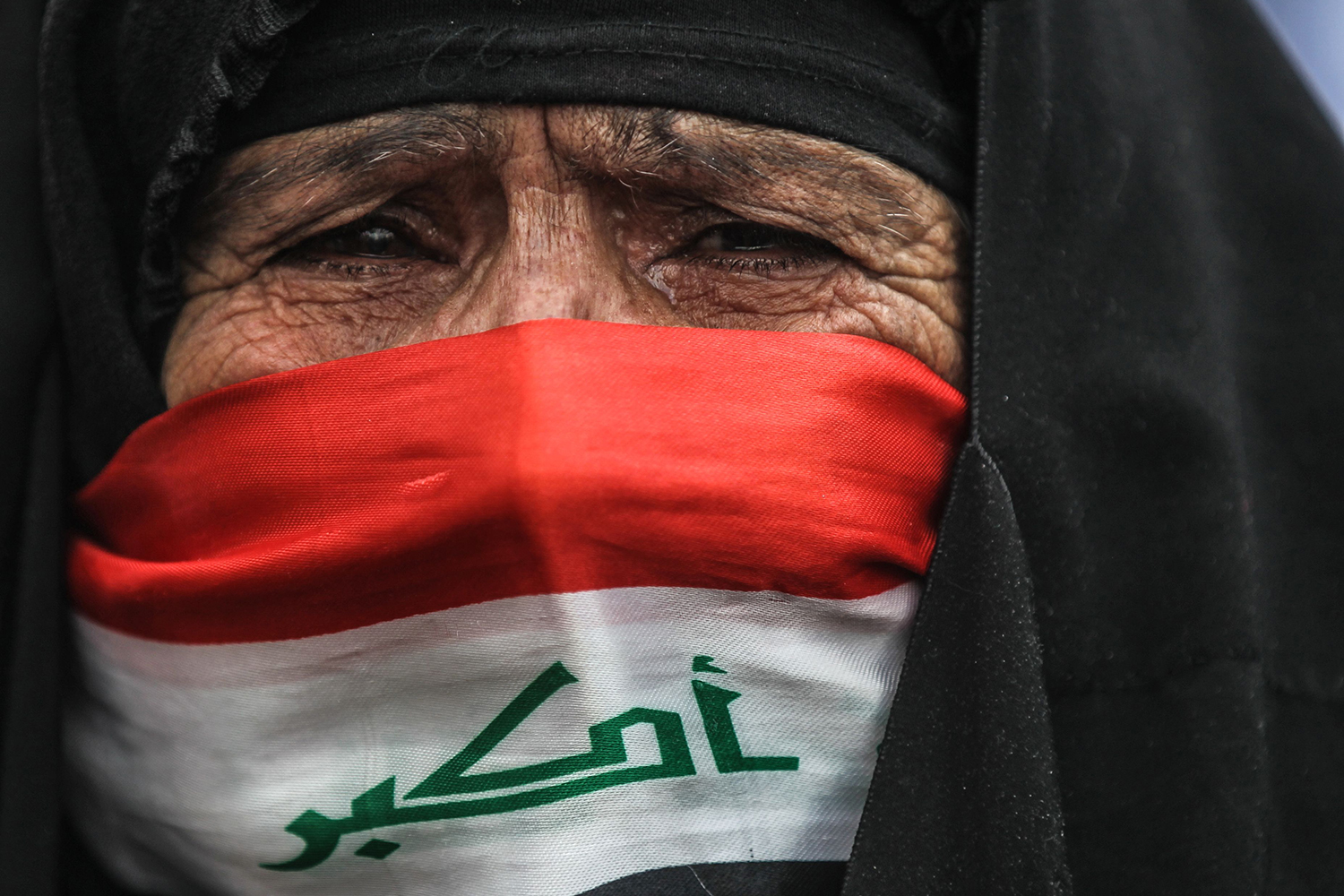 An Iraqi woman, her face covered with a national flag, cries as she watches anti-government demonstrators protest in Baghdad's Tahrir square on Jan. 10. AHMAD AL-RUBAYE/AFP via Getty Images
