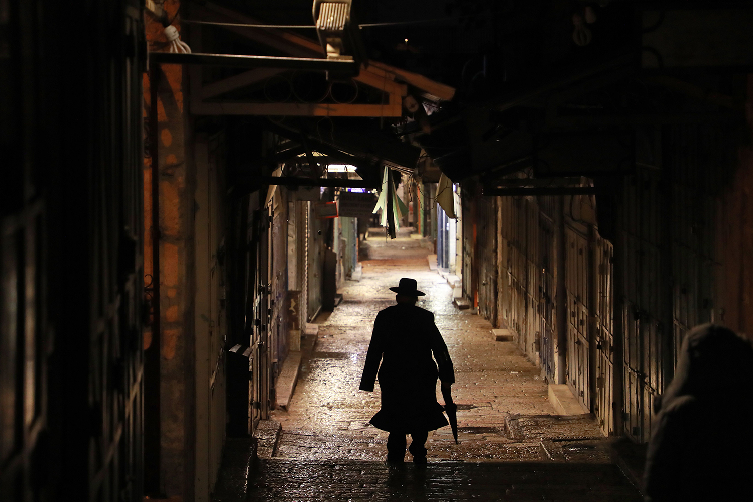 An Ultra-Orthodox Jewish man is silhouetted as he walks on an Old Jerusalem street on Jan. 20. LUDOVIC MARIN/AFP via Getty Images