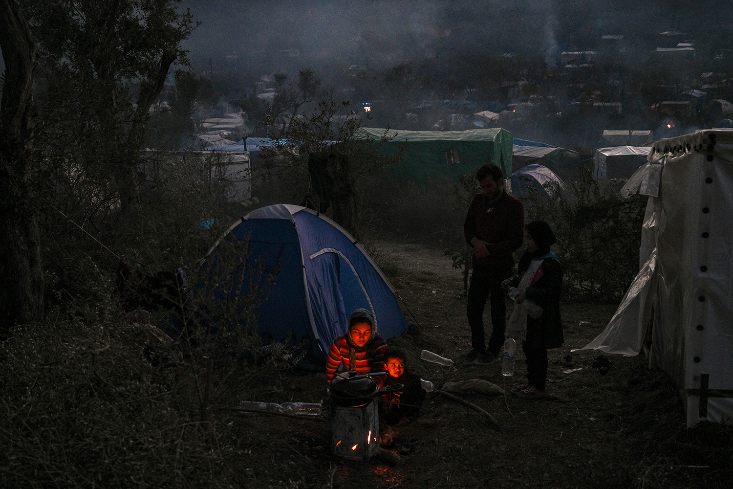 A family cooks dinner near the Moria refugee camp on the Greek island of Lesbos on Jan. 22. ARIS MESSINIS/AFP via Getty Images