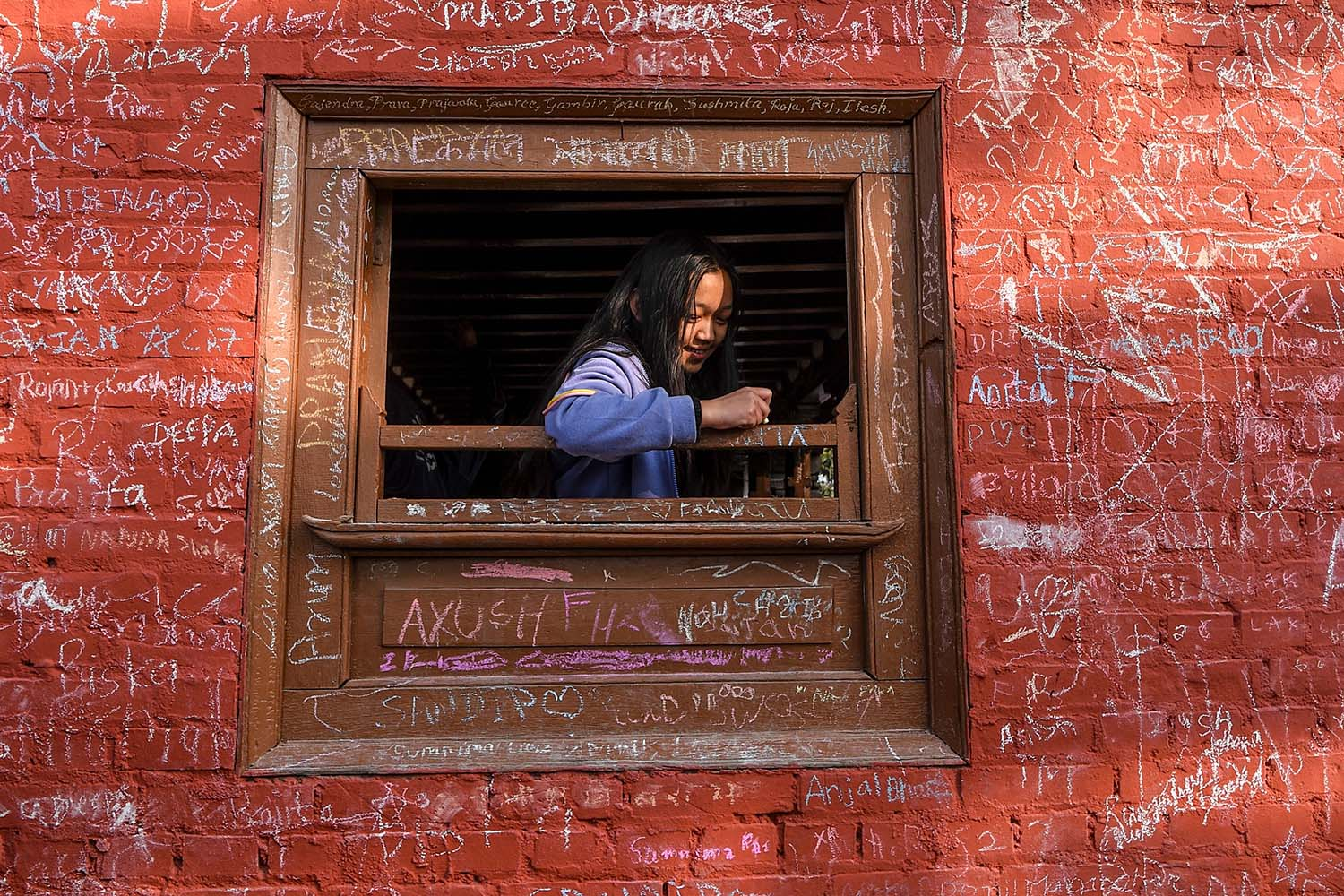 A girl writes messages with chalk on a window frame at Saraswati temple during the Hindu festival Basanta Panchami, which marks the arrival of spring, in Kathmandu on Jan. 30. PRAKASH MATHEMA/AFP via Getty Images