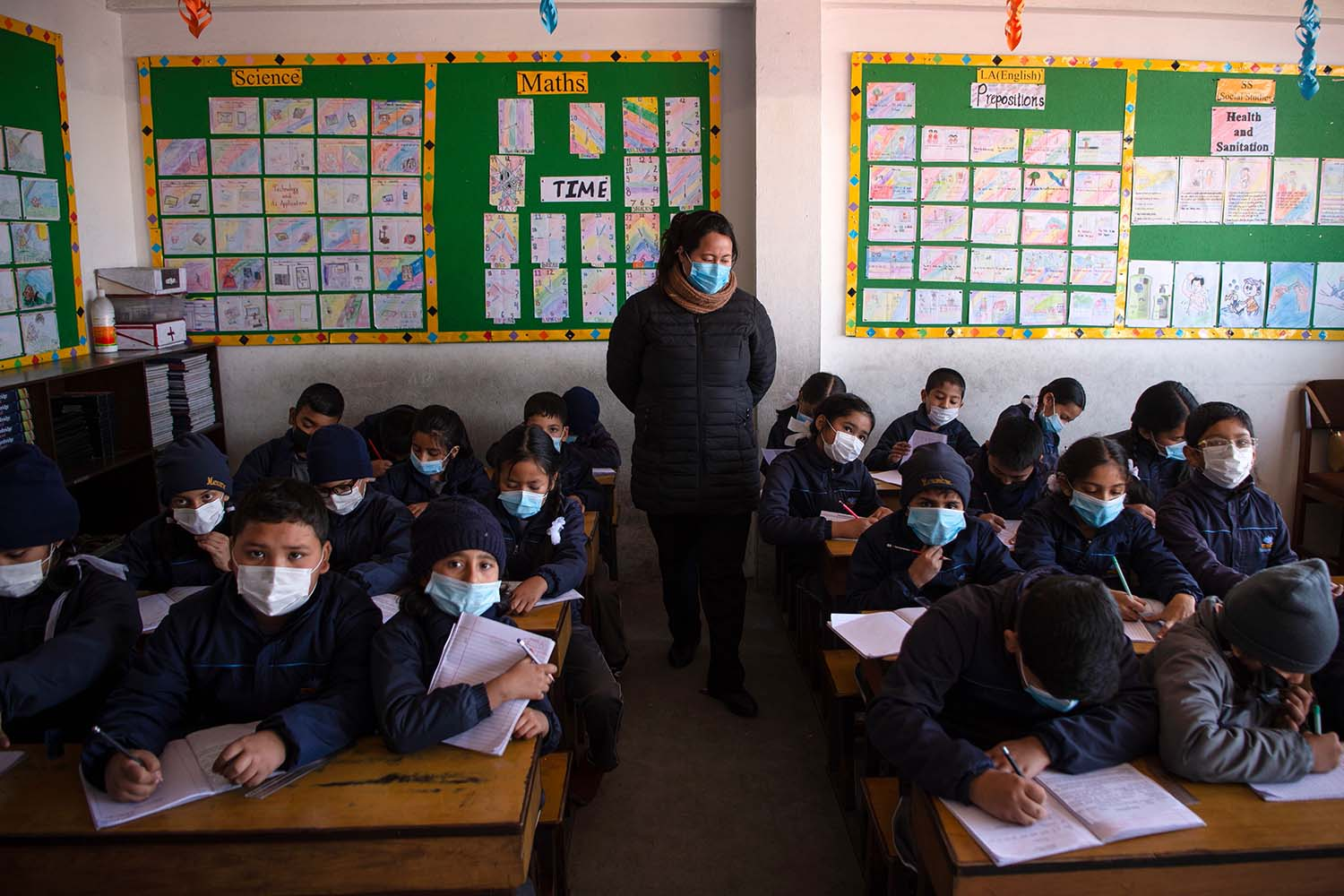 Nepali students, wearing face masks, attend a class at Matribhumi School in Bhaktapur, on the outskirts of Kathmandu, on Jan. 29 following the first confirmed case of the cornoavirus in the country. PRAKASH MATHEMA/AFP via Getty Images