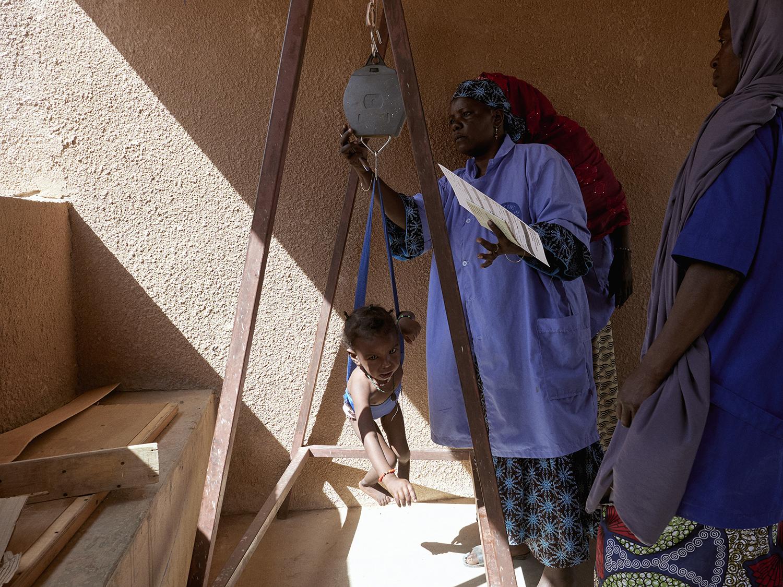 Nurses weigh children at a pediatric clinic in Agadez, Niger, on Nov. 20, 2018.