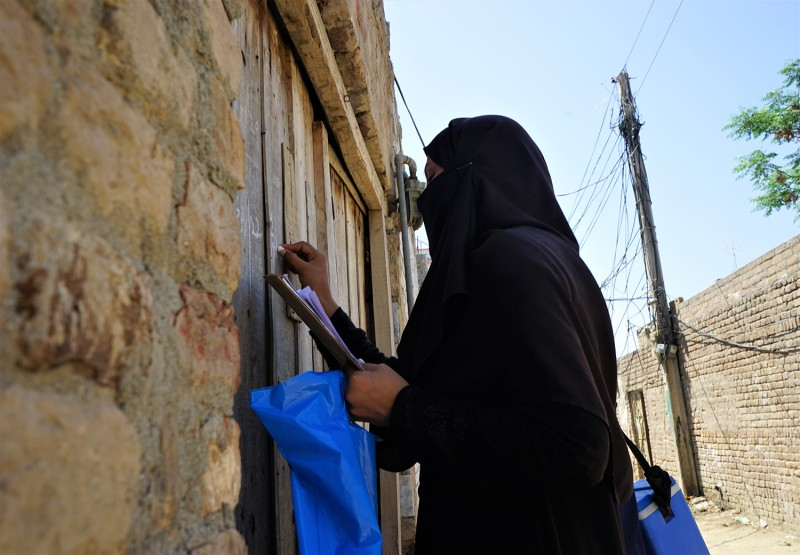 A vaccinator marks the door of a house during a polio vaccination drive in Nowshera, Pakistan, on April 22, 2019.