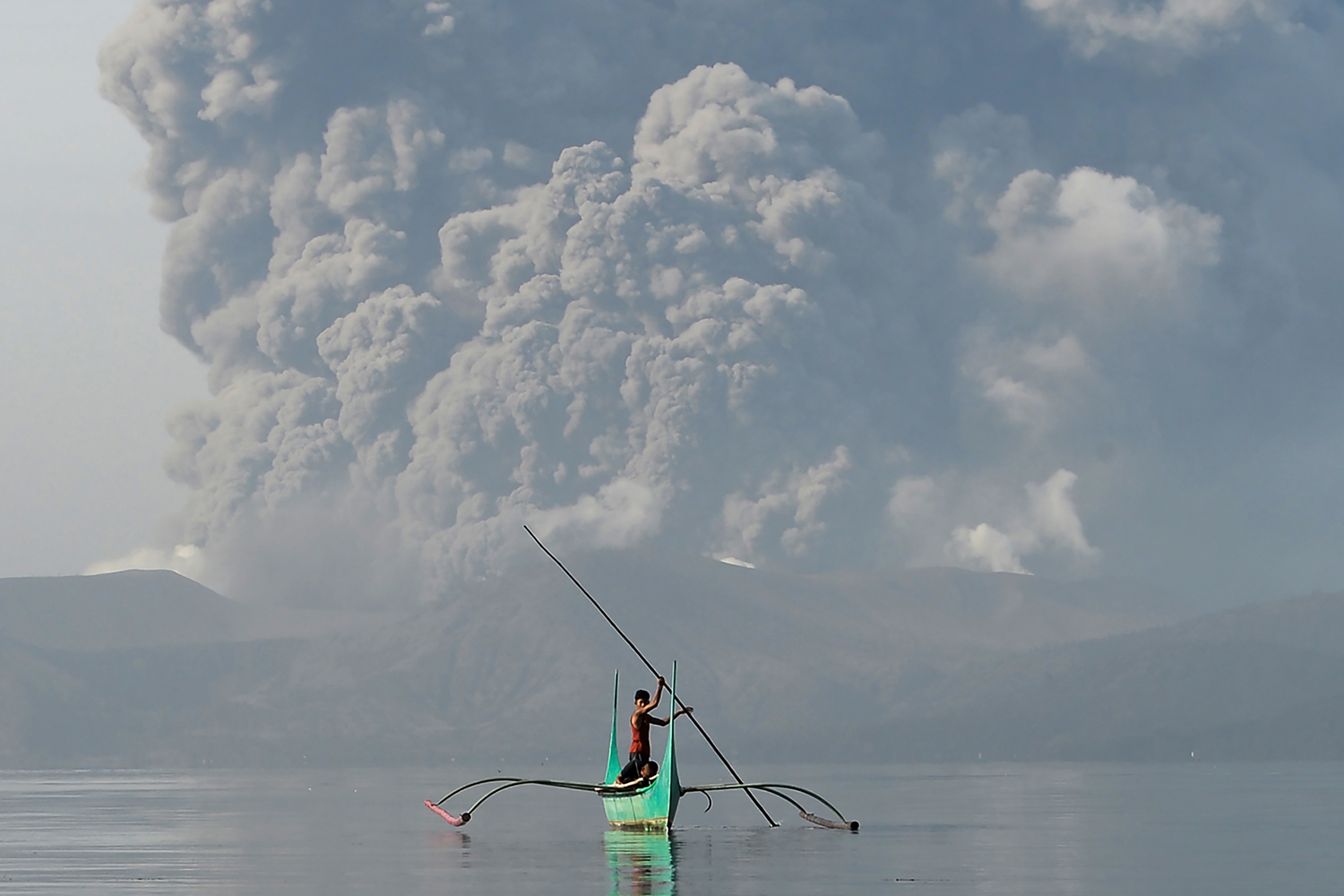 A Filipino youth rides an outrigger canoe while the Taal volcano spews ash as seen from Tanauan town in Batangas province, south of Manila, on Jan. 13. TED ALJIBE/AFP via Getty Images