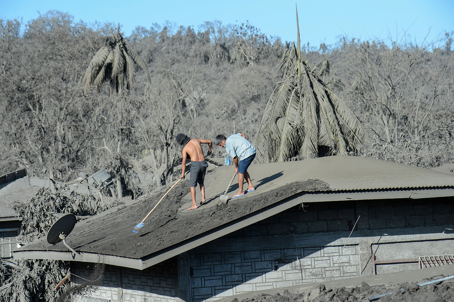 Residents work to clear the roof of their home of mud and ash due to the eruption of the nearby Taal volcano at a village in Laurel, Batangas province, in the Philippines on Jan. 16. TED ALJIBE/AFP via Getty Images