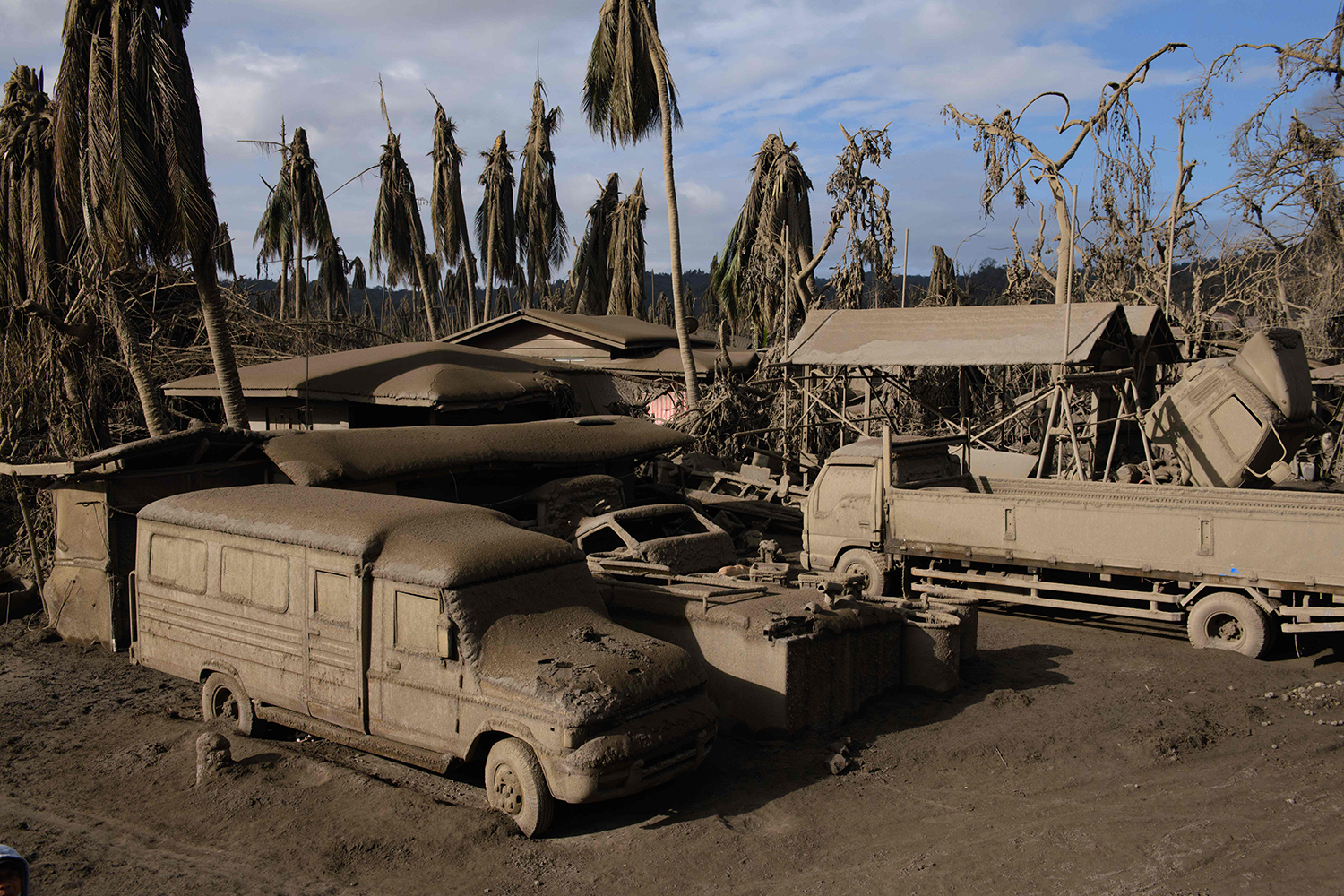 Vehicles are covered in ash from the eruption of the Taal volcano, near Agoncillo, in the Philippines on Jan. 20. ED JONES/AFP via Getty Images