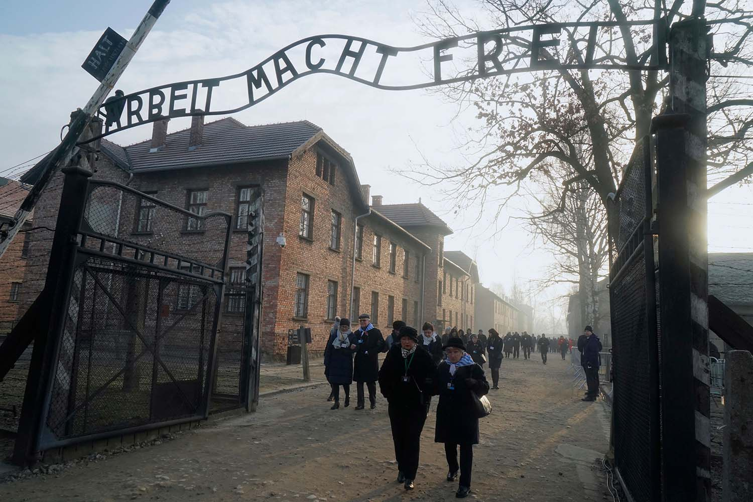 "Holocaust survivors walk below the Auschwitz gate with its inscription ""Work sets you free"" after a wreath-laying at the death wall at the memorial site of the former German Nazi death camp  in Oswiecim, Poland, on Jan. 27. More than 200 survivors from around the world planned to come to the camp for the anniversary to share their testimony as a stark warning amid a recent surge of anti-Semitic attacks on both sides of the Atlantic. JANEK SKARZYNSKI/AFP via Getty Images"