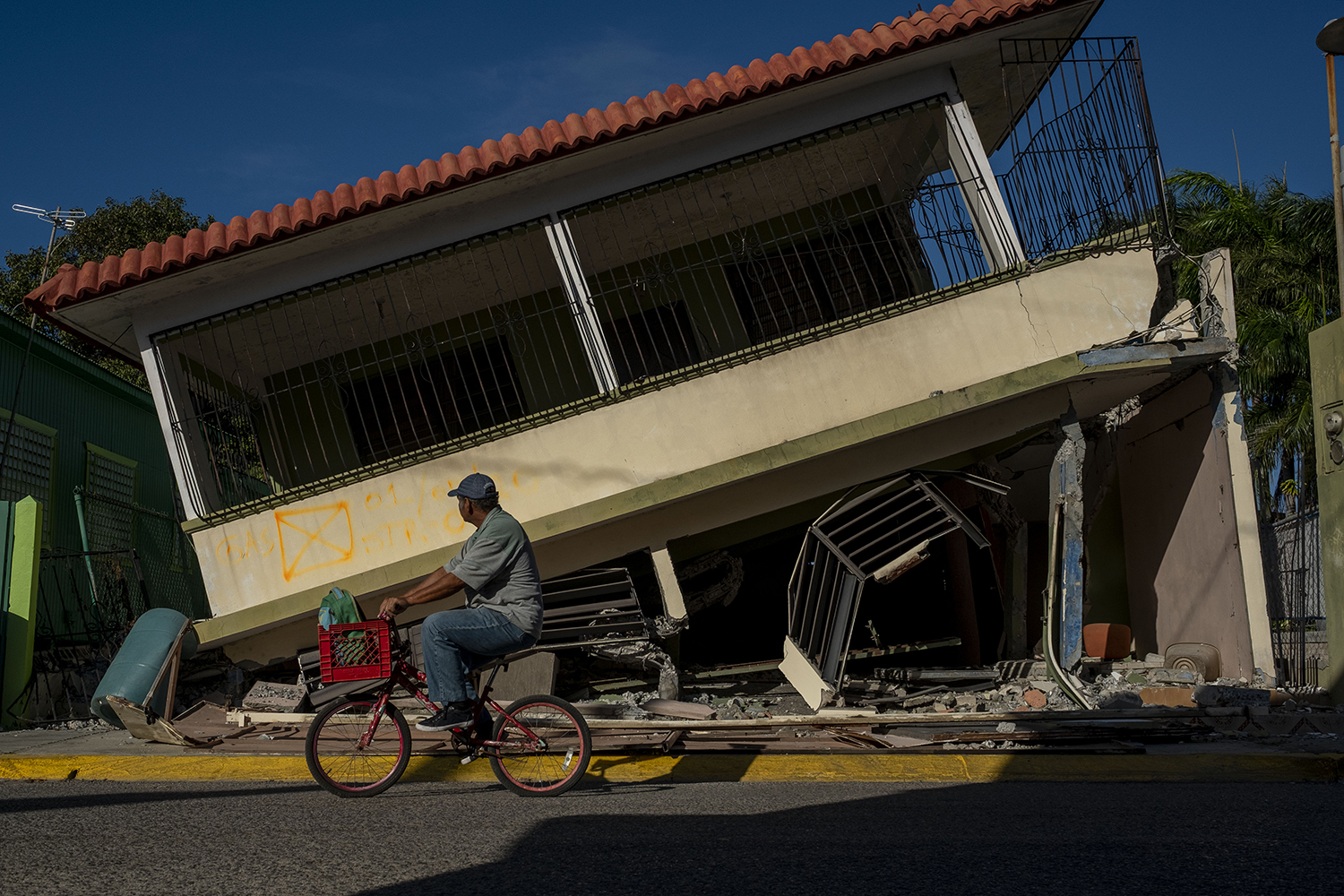 A man rides his bicycle pass past a collapsed house in Guanica, Puerto Rico, on Jan. 15 after a powerful earthquake hit the island. RICARDO ARDUENGO/AFP via Getty Images