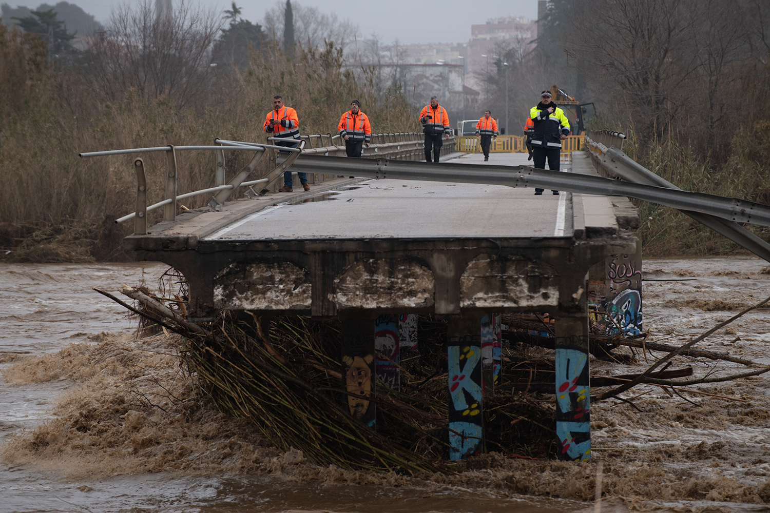 Policemen and security members walk on a fallen bridge in Malgrat de Mar near Girona, Spain, on Jan. 22. A winter storm has battered Spain's eastern coast, killing three people, cutting power, closing schools, and severing road and rail links. JOSEP LAGO/AFP via Getty Images
