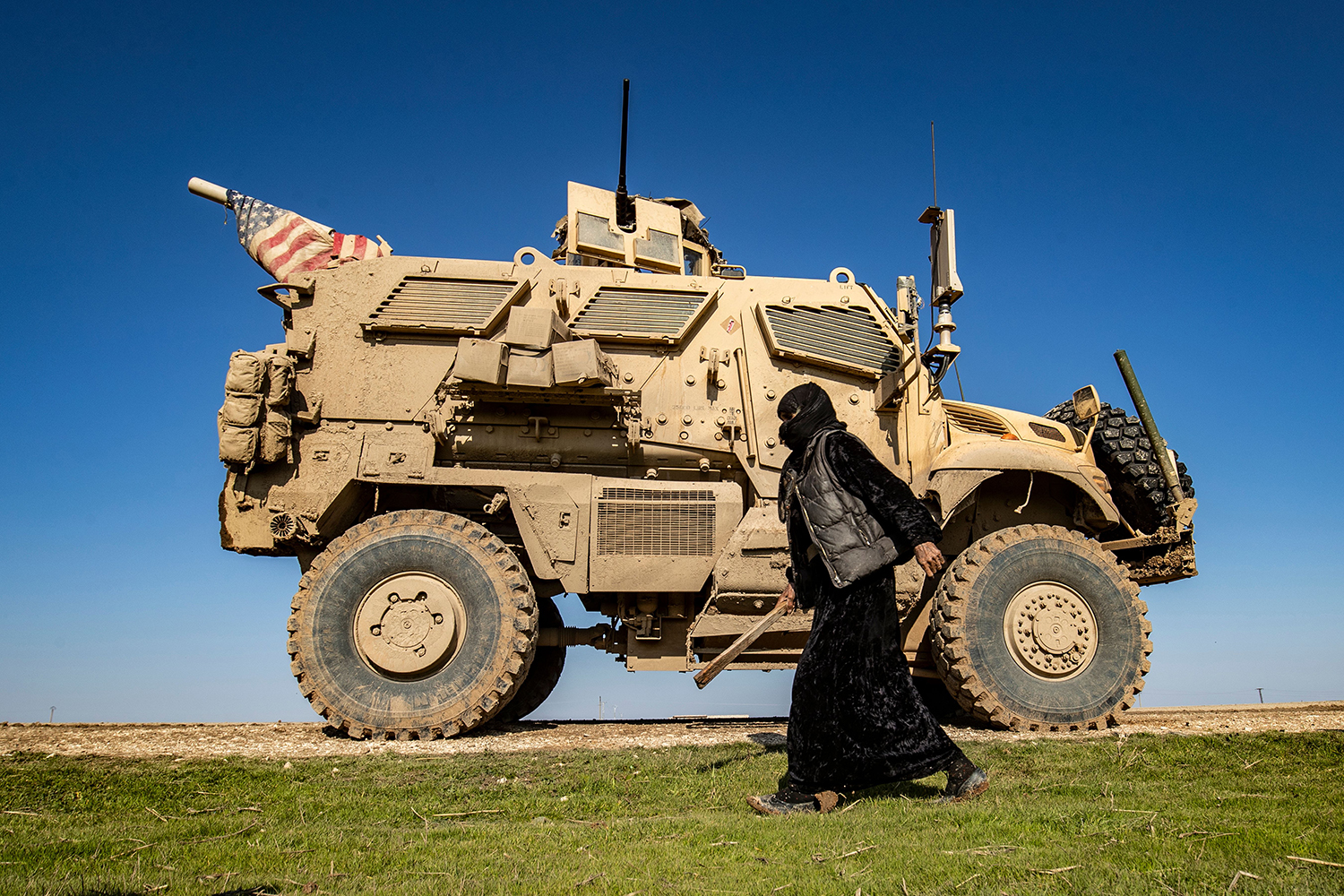 A Syrian woman walks past a U.S. military armored vehicle patrolling the village of Al-Jawadiyah in the northeastern Hasakeh province, near the border with Turkey, on Jan. 22. DELIL SOULEIMAN/AFP via Getty Images