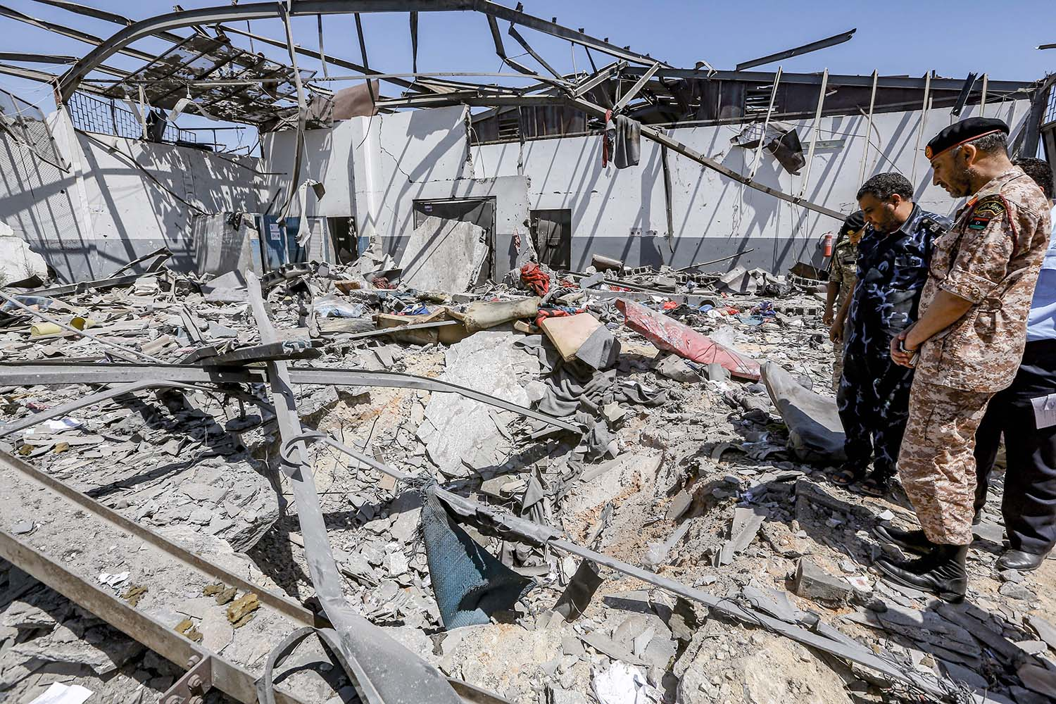 Libyan military officers inspect damage and debris at the Tajoura migrant detention center outside Tripoli after an aistrike on July 3, 2019.