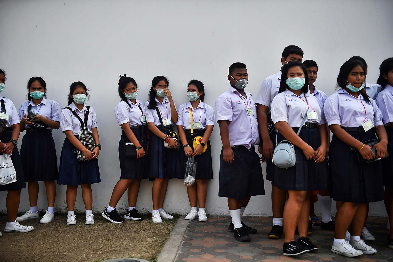 Thai students wearing face masks in efforts to stem the spread of the novel coronavirus line up in front of the Grand Palace in Bangkok on Jan. 29. LILLIAN SUWANRUMPHA/AFP via Getty Images
