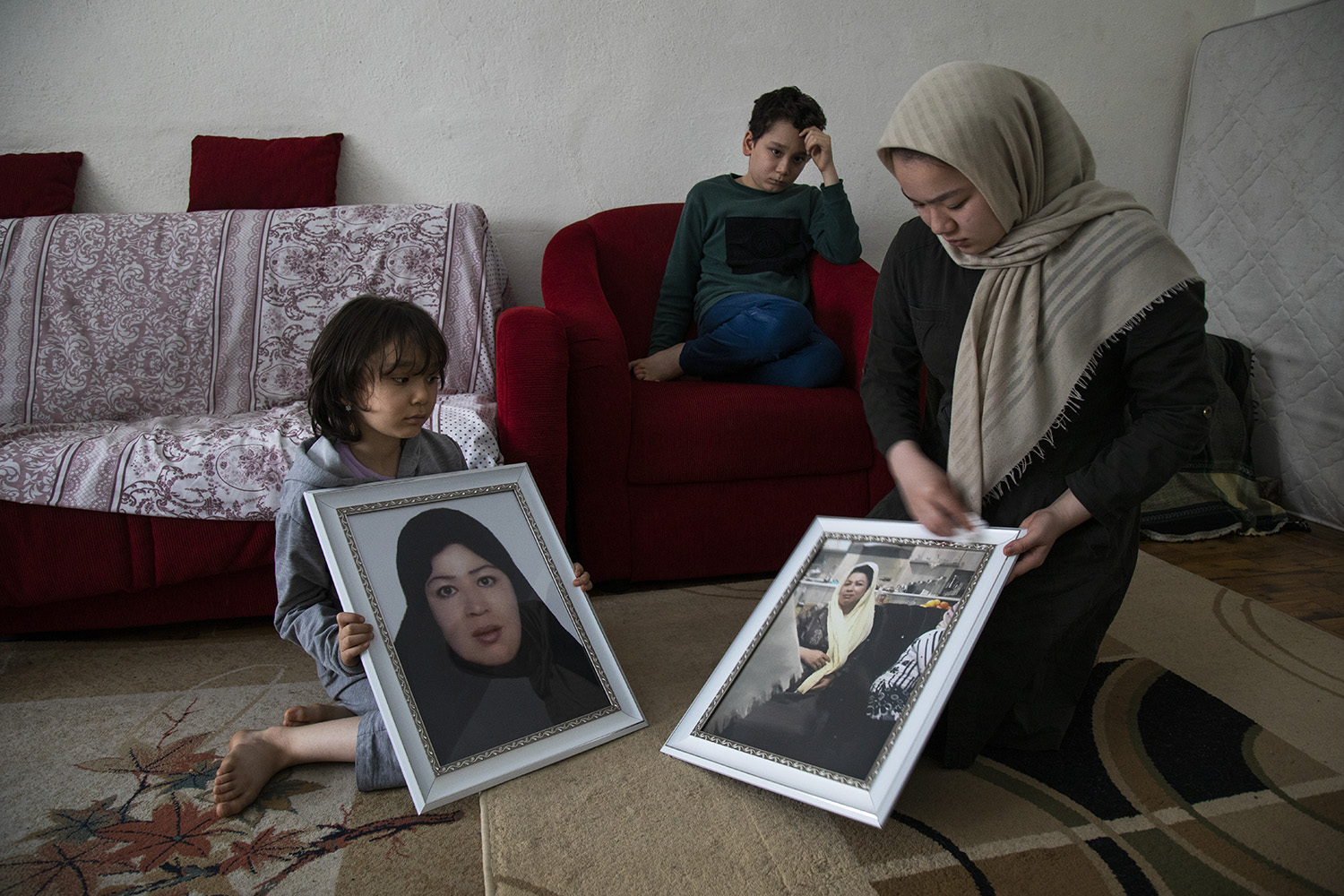 From left, members of the Ahmedzada family, 7-year-old Taiba, 11-year-old Abdolhassan, and 14-year-old Bahara, clean photographs of their mother, Roya, at their home in Turkey on April 20, 2019. The family, originally from Ghazni, Afghanistan, was crossing the Iran-Turkey border when they became separated. Roya handed the two younger children to their father to carry them across a mountain stream before she was swept away. Weeks later, her body was found by Iranian border guards. Authorities said she had been shot and killed.