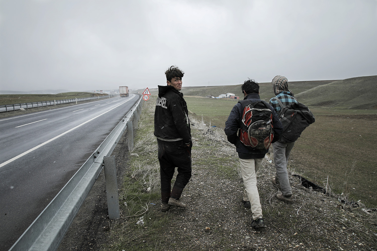 Afghan men walk along the highway between the Turkish cities of Dogubayazit and Agri, in eastern Turkey, near the border with Iran on April 22, 2019. After crossing the border, they were unable to obtain proper documentation that would allow them to ride public transportation, forcing them to walk for hours or days as they travel toward Istanbul on their way to Europe.