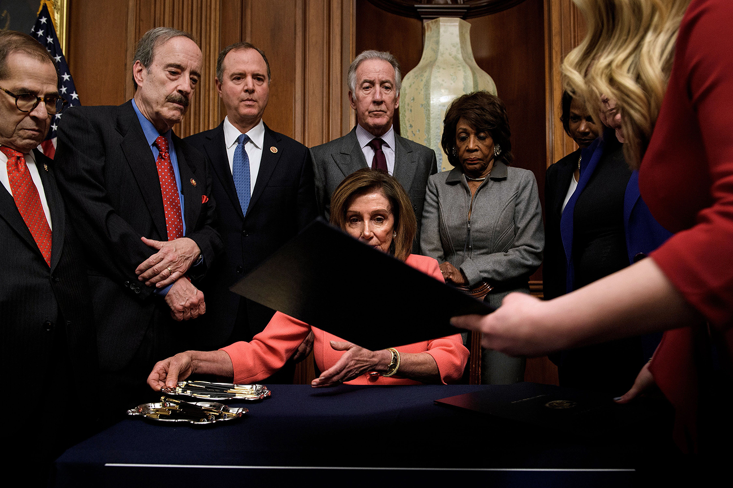 U.S. Speaker of the House Nancy Pelosi is handed a document while signing the articles of impeachment of President Donald Trump during a ceremony on Capitol Hill in Washington on Jan. 15. BRENDAN SMIALOWSKI/AFP via Getty Images
