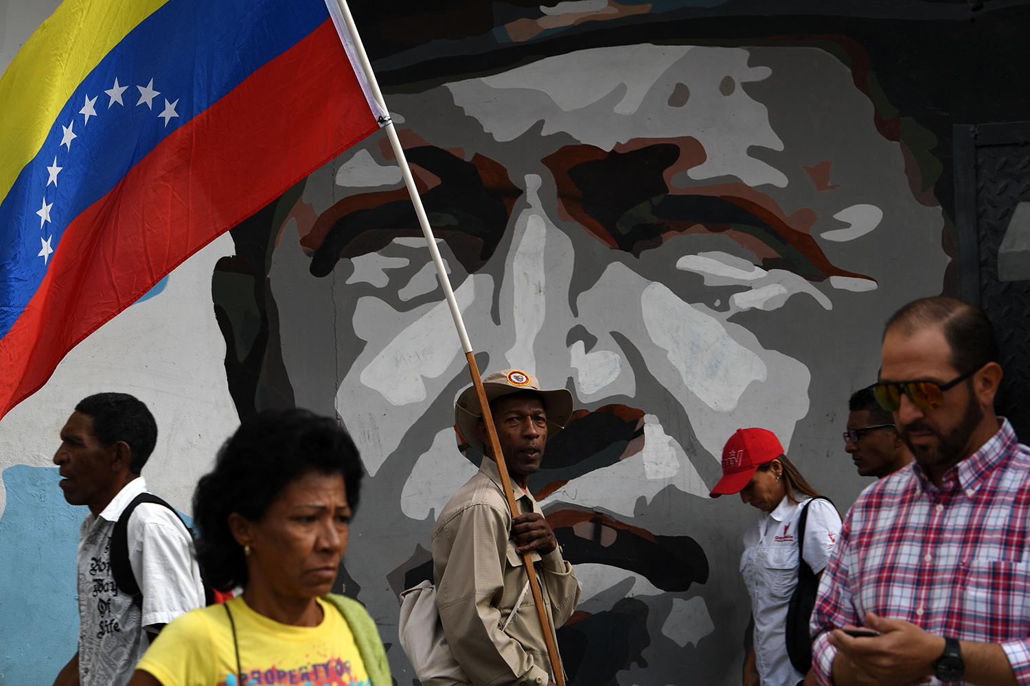 A member of the Bolivarian militia holds a Venezuelan flag as he passes a mural depicting Venezuelan late President Hugo Chavez during a march in support of Venezuelan President Nicolas Maduro in Caracas on Jan. 14. YURI CORTEZ/AFP via Getty Images