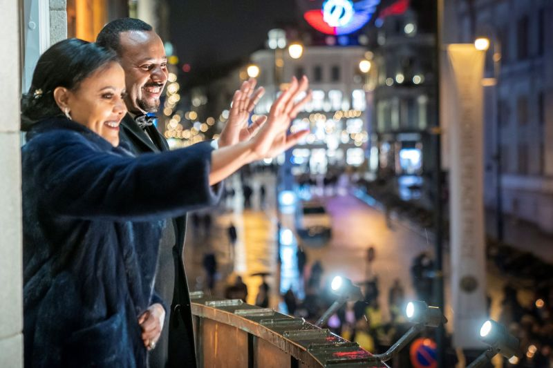 Ethiopia's Prime Minister and Nobel Peace Prize Laureate Abiy Ahmed (R) and his wife, Zinash Tayachew, wave to the crowd from the balcony of the Grand Hotel in Oslo on Dec. 10, 2019