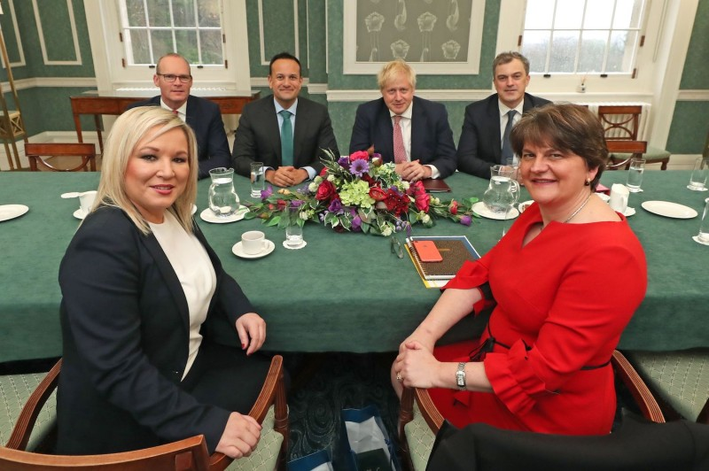 Northern Ireland's new deputy First Minister Michelle O'Neill (left) and First Minister Arlene Foster (right) meet with members of the British and Irish governments in Belfast, Northern Ireland, after signing a deal to restore power-sharing.
