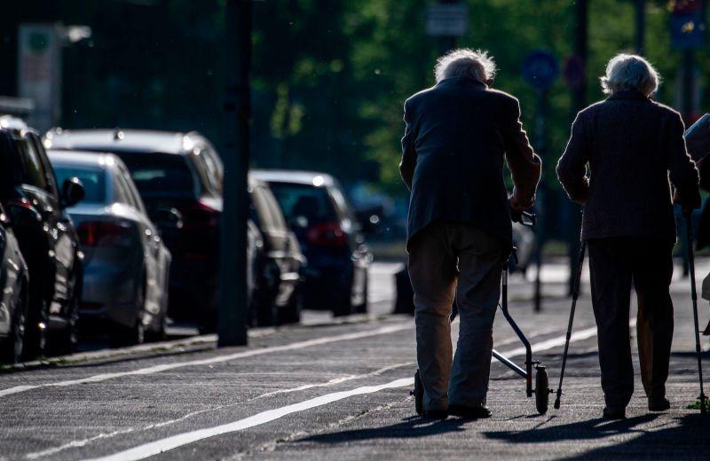 An elderly couple walks into the sunset on a boulevard.