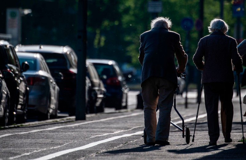 An elderly couple walks into the sunset on a boulevard.
