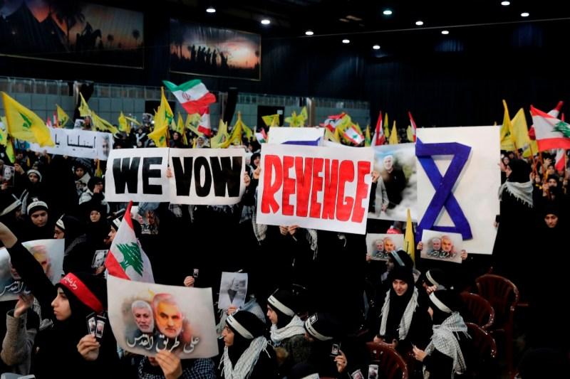 Supporters of Hezbollah hold placards calling for revenge for the killing of Qassem Suleimani in Beirut, Lebanon.