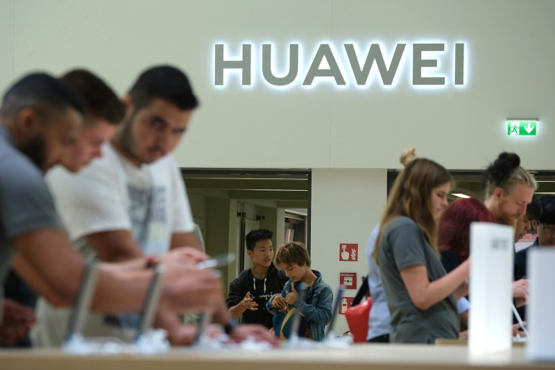 Visitors check out new Huawei smartphones at the 2019 IFA home electronics and appliances trade fair on Sept. 6, 2019 in Berlin, Germany.