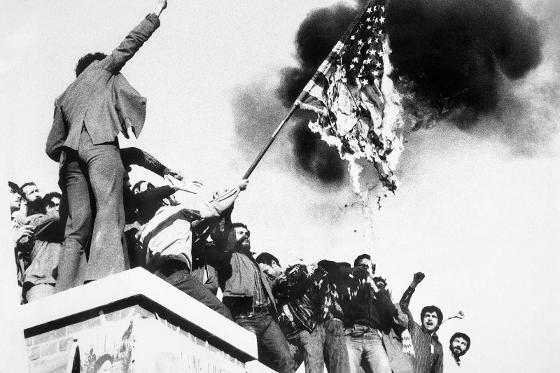 Demonstrators burn a U.S. flag as they stand atop the wall of the U.S. Embassy in Tehran on Nov. 9, 1979, after storming the embassy and taking hostages. Bettmann Archive/Getty Images