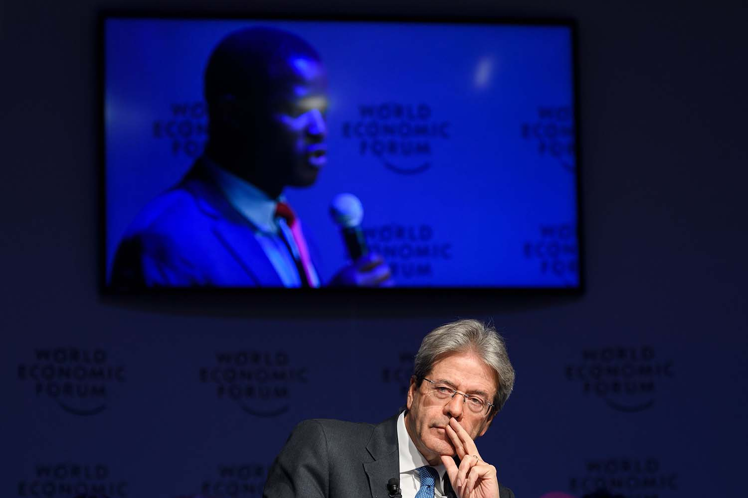 Then-Italian Prime Minister Paolo Gentiloni listens to a refugee seen on the screen behind him during a session on mass migration across the Mediterranean during the annual World Economic Forum in Davos, Switzerland, on Jan. 24, 2018. FABRICE COFFRINI/AFP via Getty Images