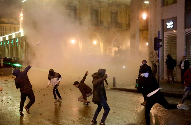 Lebanese protesters throw stones at riot police in central Beirut on Jan. 19.